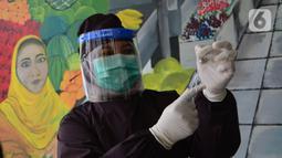 Paramedis dari Unit Pelaksana Teknis Dinas (UPTD) Puskesmas Cisalak Pasar menyiapkan vaksin Covid-19 untuk para pedagang di Pasar Cisalak, Depok, Jawa Barat, Selasa (09/03/2021). Pemkot Depok melakukan vaksinasi Covid-19 kepada 213 pedagang di empat pasar tradisional. (merdeka.com/Arie Basuki)