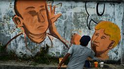 Seniman melukis mural yang menggambarkan senator Australia, Fraser Anning dipukul kepalanya menggunakan sebutir telur oleh William Conolly, di Banda Aceh, Aceh, Kamis (21/3/2019). (CHAIDEER MAHYUDDIN/AFP)
