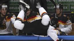 Pemain Ice Hockey Jerman, Korbinian Holzer terlempar keluar arena saat berebut bola dengan pemain Rusia pada kejuaraan IIHF World Championship 2016 di Moscow, Rusia, (19/5/2016). (REUTERS/Grigory Dukor)