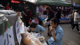 Dua wanita menikmati makan siang di pasar di Beijing (20/11). (AFP Photo/Nicolas Asfouri)