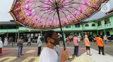Warga antre dengan mengikuti physical distancing untuk mendapatkan bantuan beras di Makodim 0506 Tangerang, Banten, Senin (27/4/2020). Program bantuan melalui ATM Pertanian Si Komandan memiliki kapasitas muat 180 kilogram dengan waktu operasi selama 12 jam per hari. (Liputan6.com/Fery Pradolo)