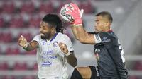 Pemain Arema FC, Carlos Fortes (kiri) berebut bola dengan kiper Persija, Andritany Ardhiyansa saat laga pekan ketujuh BRI Liga 1 2021/2022 di Stadion Manahan, Solo, Minggu (17/10/2021). (Bola.com/B