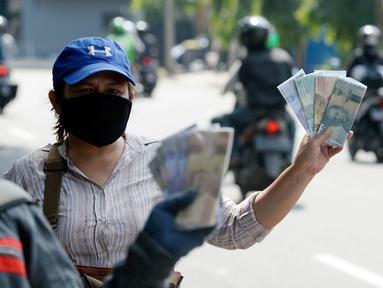 Penjual jasa penukaran uang menawarkan uang baru berbagai pecahan kepada pengguna jalan di kawasan Bintaro Sektor 2, Jakarta Selatan, Selasa (12/05/2020). Menjelang perayaan Lebaran, jasa penukar uang keliling yang berada di pinggir jalan-jalan utama mulai bermunculan. (merdeka.com/Dwi Narwoko)