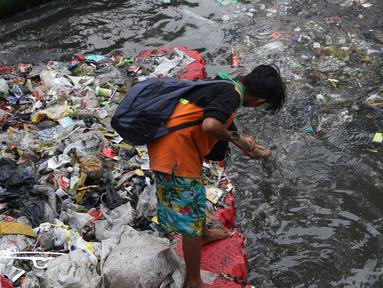 Salah satu petugas UPK Badan Air Dinas Lingkungan Hidup DKI Jakarta mengangkut ceceran sampah di Kali Cideng, Jakarta, Jumat (9/11). Pembersihan untuk mencegah terjadinya penumpukan sampah saat musim hujan di Jakarta. (Liputan6.com/Helmi Fithriansyah)