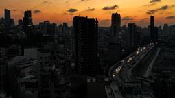 Gambar pada 11 Oktober 2021 menunjukkan pemandangan senja saat mobil-mobil yang melaju melewati gedung-gedung gelap di sepanjang jalan raya Charles Helou di pelabuhan yang hancur di ibu kota Lebanon, Beirut, dalam kegelapan selama pemadaman listrik. (AFP)
