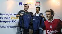Perwakilan Manajemen AXA Mandiri Hartono memberikan jaket kepada pemain legendaris Liverpool Vladimir Smicer pada sharing and learning kepada anak-anak U-12 di Grand Futsal, Jakarta, Jumat (8/2). (Liputan6.com/Fery Pradolo)