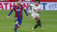 Pemain Barcelona Lionel Messi memperebutkan bola dengan pemain Sevilla Jules Kounde pada pertandingan semifinal Copa del Rey Spanyol di stadion Ramon Sanchez Pizjuan di Seville, Spanyol, Rabu, 10 Februari 2021. (Foto AP / Angel Fernandez)