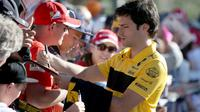 Pembalap tim Renault Carlos Sainz Jr. memberikan tanda tangan kepada fans sesaat sebelum latihan bebas Formula 1 (F1) GP Australia di Melbourne, Jumat (23/3). Balapan F1 GP Australia 2018 sendiri akan bergulir pada Minggu, 25 Maret besok (AP/Rick Rycroft)