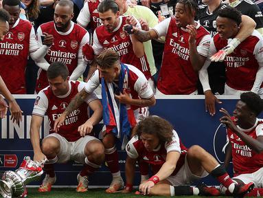 Pierre-Emerick Aubameyang dari Arsenal bereaksi saat menjatuhkan trofi pada perayaan gelar juara Piala FA usai mengalahkan Chelsea pada laga final Piala FA di stadion Wembley, Minggu (2/8/2020).  Aubameyang terlihat kaget sambil memegang kepalanya saat trofi terjatuh. (Catherine Ivill/POOL/AFP)