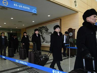 Rombongan grup orkestra Korea Utara tiba di kantor transit Korea di dekat Zona Demiliterisasi (DMZ) yang membagi kedua Korea di Paju (5/2). 140 anggota orkestra Korut akan tampil pada perhelatan Olimpiade Musim Dingin 2018. (AFP Photo/Pool/Jung Yeon-Je)