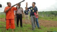 Salah seorang tersangka, Nasir, 55, memeragakan dirinya menembak orang utan, saat rekonstruksi Februari lalu. (dok. Bontang Post/Jawa Pos Group)