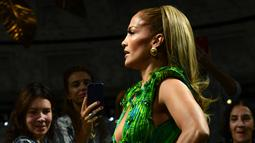 Bintang pop dan aktris, Jennifer Lopez mengenakan gaun Versace untuk Spring/Summer Collection 2020 pada Milan Fashion Week 2019, Jumat (20/9/2019). Jennifer Lopez mengenakan versi baru gaun hijau ikonis yang pernah ia gunakan di Grammy Awards 20 tahun lalu. (Miguel MEDINA/AFP)