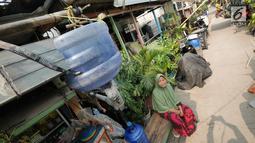 Warga duduk di bawah talang air kawasan Kampung Kamal Muara, Jakarta, Selasa (9/7/2019). Saat musim kemarau, warga Kampung Kamal Muara harus membeli air seharga Rp 5.000 per jeriken untuk kebutuhan mandi, cuci pakaian dan lain-lain. (Liputan6.com/Herman Zakharia)