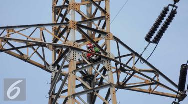 Seorang pria berada di atas menara sutet di kawasan Pasar Senen, Jakarta, Selasa (27/9). Pria nekat tersebut berencana memasang bendera merah putih dengan sebuah kalimat berisi permintaan untuk menghukum oknum Dandim. (Liputan6.com/Gempur M Surya)