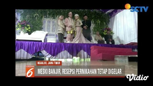 Pasangan di Nganjuk, Jawa Timur, gelar pesta pernikahan di tengah genangan banjir.