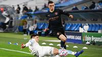 Gelandang Manchester City, Phil Foden, berebut bola dengan bek Olympique Marseille, Leonardo Balerdi, pada laga Liga Champions 2020/2021 di Stadion velodrome, Rabu (28/10/2020) dini hari WIB. Manchester City menang 3-0 atas Marseille. (AFP/Christophe Simon)