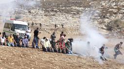 Pengunjuk rasa Palestina melaksanakan salat di tengah tembakan gas air mata oleh tentara Israel di dekat desa Beit Dajan, timur Nablus, Palestina (9/10/2020). (AFP/Jaafar Ashtiyeh)