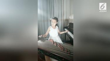 Seorang gadis berusia 9 tahun piawai bermain 2 alat musik sekaligus. Ia memainkan piano dan kecapi China  secara bersamaan.
