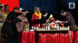 Ketua Umum PDI Perjuangan Megawati Soekarnoputri (kedua kanan) menyerahkan potongan tumpeng kepada Presiden Joko Widodo disaksikan Wakil Presiden Ma'ruf Amin (keempat kiri) saat pembukaan Rakernas I dan HUT ke-47 PDIP di JIEXPO Kemayoran, Jakarta, Jumat (10/1/2020). (Liputan6.com/Johan Tallo)
