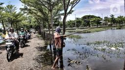 Rombongan pengantar jenazah melintas di dekat Amir yang tengah memancing di TPU Semper, Jakarta, Selasa (2/2/2021). Banjir tersebut dimanfaatkan warga setempat untuk mencari ikan dengan menggunakan alat pancing serta jala. (merdeka.com/Iqbal S. Nugroho)