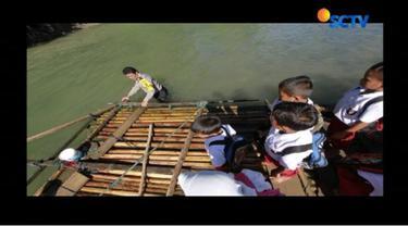 Aipda Ismet rela membantu puluhan siswa SDN 1 Bulano Ulu, Kabupaten Bone Bolango saat menyeberang sungai.
