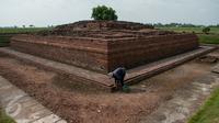 Pekerja melakukan perawatan rutin Candi Jiwa, Batujaya, Karawang, Jawa Barat (9/5). Candi Jiwa tidak terbuat dari batu, namun dari lempengan-lempengan batu bata dan Candi Jiwa merupakan peninggalan kerajaan Tarumanegara. (Liputan6.com/Gempur M Surya)