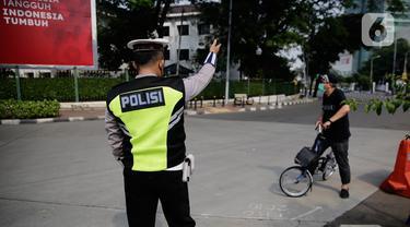 Petugas gabungan mengarahkan pengguna sepeda saat pengalihan jalur pesepeda di kawasan Sudirman-Thamrin, Jakarta, Minggu (5/9/2021). Pemberlakuan jalur ganjil genap pada masa PPKM membuat pengguna sepeda dilarang melintasi kawasan ganjil-genap pagi ini. (Liputan6.com/Angga Yuniar)