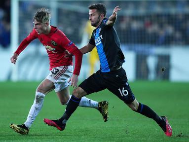 Bek kiri Manchester United, Brandon Williams, berebut bola dengan pemain Club Brugge, Siebe Schrijvers dalam leg pertama babak 32 besar Liga Europa di Jan Breydelstadion, Kamis (20/2/2020). Manchester United gagal meraih hasil maksimal usai ditahan imbang Club Brugge 1-1. (AP/Francisco Seco)