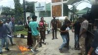 seorang mahasiswa demonstrasi di Kejati Sulawesi Tenggara, kena hantaman ember oleh petugas saat melakukan aksi protes.(Liputan6.com/Ahmad Akbar Fua)