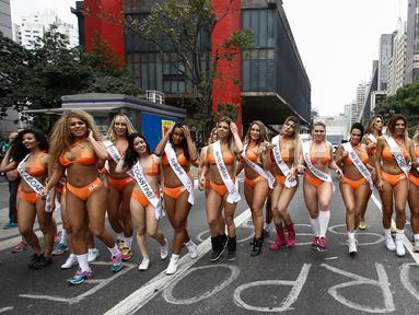 Sejumlah wanita seksi menyusuri jalanan di Sao Paulo, Senin (8/8). Mengenakan bikini, para wanita tersebut mempromosikan kontes Miss BumBum 2016 yaitu kontes yang menganugerahi wanita dengan pantat terindah seantero Brasil. (Miguel SCHINCARIOL/AFP)