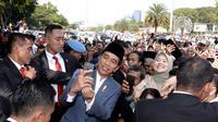 Presiden Joko Widodo atau Jokowi yang menggelar open house di Istana Negara, keluar untuk berfoto bersama warga, Rabu (6/5/2019) (Liputan6/Lizsa Egeham)