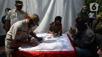 Aparat gabungan mendata pelanggar yang terjaring razia saat Operasi Yustisi di Kawasan Danau Sunter, Jakarta, Rabu (16/9/2020). Warga yang tidak memakai masker langsung disidang tindak pidana ringan (tipiring) di tempat dengan membayar denda Rp 55.000 maupun sanksi sosial. (merdeka.com/Imam Buhori)