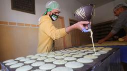 Warga membuat penganan manis tradisional yang dikenal dengan nama Qatayef di Kota Rafah, Jalur Gaza, Palestina, Senin (27/4/2020). Qatayef adalah sejenis makanan penutup khas Arab yang biasa dibuat saat bulan suci Ramadan. (Xinhua/Khaled Omar)
