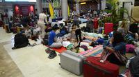 Turis asing bersantai dengan alas seadanya di lantai Bandara Internasional Lombok Praya, NTB, Senin (6/8). Imbas gempa 7 skala Richter, para wisatawan mancanegara terlantar di bandara karena jam pemberangkatan pesawat yang tertunda. (AFP/SONNY TUMBELAKA)