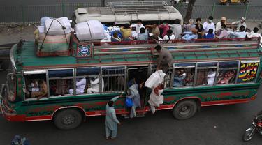 Warga menaiki bus saat mereka melakukan perjalanan ke kampung halaman mereka menjelang perayaan Idul Fitri di Lahore (7/5/2021). Lebaran Idul Fitri jatuh pada 13 Mei 2021. (AFP Photo/Arif Ali)
