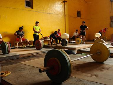Sejumlah atlet angkat besi dan berat melakukan latihan di luar gedung PB PABBSI, Stadion GBK Jakarta, Senin (11/1/2016). Latihan dilakukan diluar gedung akibat proses renovasi gedung PB PABBSI. (Liputan6.com/Helmi Fithriansyah)