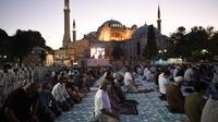 Umat Islam, memanjatkan doa-doa mereka selama salat Idul Adha, dengan latar belakang Hagia Sophia, yang baru-baru ini dikonversi kembali ke masjid, di distrik bersejarah Sultanahmet di Istanbul, 31 Juli 2020.  (AP Photo/Yasin Akgul)
