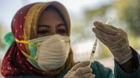 Seorang dokter bersiap untuk memberikan vaksin virus corona COVID-19 Sinovac di klinik vaksinasi massal darurat di lapangan sepak bola di Surabaya, Jawa Timur, Selasa (6/7/2021). Indonesia tengah memerangi gelombang infeksi baru yang belum pernah terjadi sebelumnya. (JUNI KRISWANTO/AFP)