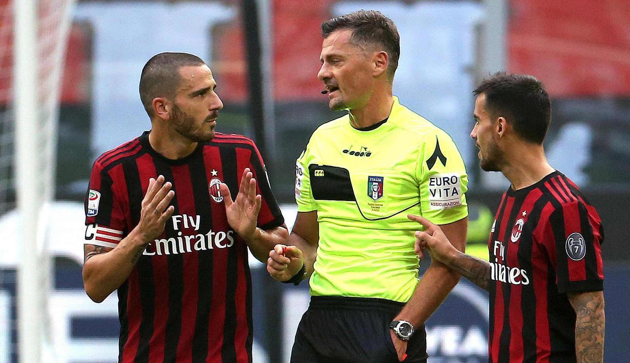 Bek AC Milan, Leonardo Bonucci (kiri) berbincang dengan wasit Piero Giacomelli setelah menerima kartu merah saat bertanding melawan Genoa pada lanjutan Liga Italia di San Siro, Milan (22/10). Bonucci di kartu merah menit 25. (Matteo Bazzi/ANSA via AP)