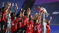 Kapten Bayern Munchen, Manuel Neuer, mengangkat trofi saat selebrasi juara Liga Champions di Stadion The Luz, Portugal, Senin (24/8/2020). Bayern Munchen berhasil menjadi juara usai menaklukkan PSG 1-0. (David Ramos/Pool via AP)