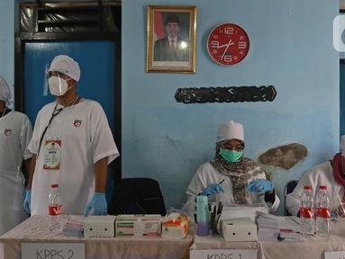 Petugas menggunakan atribut dokter saat Pilkada Depok di Tempat Pemungutan Suara (TPS) 56, Mekarjaya, Depok, Rabu (9/12/2020). TPS dengan tema kesehatan itu bertujuan menarik warga menggunakan hak pilih dan mengingatkan protokol kesehatan di masa Pandemi COVID-19.  (Liputan6.com/Herman Zakharia)