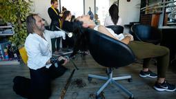 Penata rambut, Alberto Olmedo memotong rambut pelanggannya menggunakan pedang samurai di Madrid, Spanyol, 29 Desember 2018. Olmedo memilih menggunakan pedang samurai, api dan cakar besi untuk mewujudkan gaya rambut impian pelanggan. (AP/Manu Fernandez)