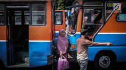 Seorang wanita melintas diantara Metromini di Terminal Blok M, Jakarta, Rabu (26/7). Menurut pihak Dishub DKI, revitalisasi tersebut melibatkan langsung para pemilik kendaraan Metromini. (Liputan6.com/Faizal Fanani)