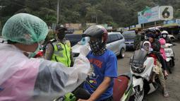 Petugas mengecek suhu tubuh pengendara saat penyekatan arus lalu lintas di Ciloto, Cianjur, Jawa Barat, Jumat (17/4/2020). Pemkab Cianjur melakukan pengecekan suhu tubuh dan penyemprotan disinfektan di titik keluar-masuk Cianjur untuk mencegah penyebaran COVID-19. (merdeka.com/Arie Basuki)