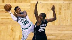 Pemain Boston Celtics, Marcus Smart (36) berusaha memasukan bola saat diadang pemain Milwaukee Bucks, Khris Middleton (22) pada laga playoffs NBA basketball di TD Garden, Boston, (24/4/2018). Celtics menang  92-87. (AP/Charles Krupa)