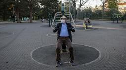 Seorang lansia berolahraga di sebuah taman di Beograd, Serbia (21/4/2020). Waktu tersebut bisa dimanfaatkan untuk berolahraga di taman atau jalan-jalan ringan dengan jarak maksimum 600 meter dari tempat tinggal. (AFP/Oliver Bunic)