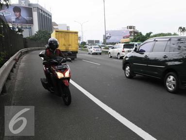 Seorang pengendara motor memasuki jalan tol arah Merak dari persimpangan Taman Anggrek, Jakarta (4/2). Minimnya rambu-rambu lalulintas jalan menuju tol Merak membuat pengendara motor tidak mengetahuinya. (Liputan6.com/Helmi Afandi)