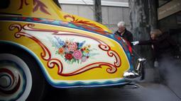 Rolls-Royce limusin touring Phantom V milik John Lennon dimasukan untuk ditampilkan di Museum Royal BC di Victoria, British Columbia (27/1/2020). Bagian pelek mobil ini juga dicat dengan warna senada dengan bodi. (Chad Hipolito/The Canadian Press via AP)