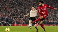 Penyerang Liverpool, Mohamed Salah melepaskan tendangan ke arah gawang Manchester United (MU) untuk mencetak gol pada lanjutan pertandingan Liga Inggris di Anfield, Minggu (19/1/2020). Menghadapi tamunya MU di Anfield, Liverpool menang dengan skor 2-0. (AP/Jon Super)
