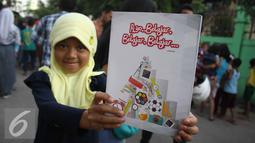 Seorang bocah memperlihatkan buku tulis yang ia peroleh dari Presiden Jokowi, Jakarta, Kamis (3/9/2015). Presiden Jokowi bersama Gubernur Ahok mengadakan blusukan dan membagikan semabko pada warga di kawasan Cilincing. (Liputan6.com/Gempur M Surya)
